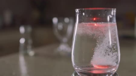 fizzing : Effervescent tablet falls into a glass with water. The tablet sparkles with colorful lights. Healthy lifestyle and medical treatment. Close-up. Slowmotion. Stock Footage