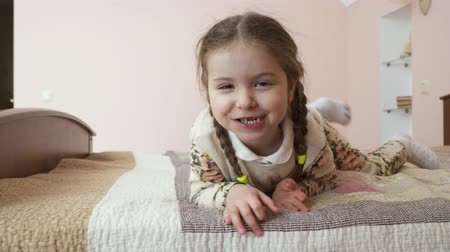 pigtail : Little girl has fun at the bed at home. Cute child is relaxing and moves along the bed. Pretty girl is boring and plays with herself. Stock Footage