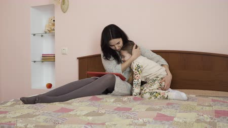 pena : Mother and little girl are hugging sitting on the bed at home. Pretty woman and adorable girl shows their feelings to each other. The woman holds digital tablet on knees.