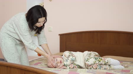 čelo : Little adorable girl lays on a bed and sleeping. The mother comes to girl and touches her head and kisses her child in forehead. Little girl is tired and falls asleep after lunch. Dostupné videozáznamy