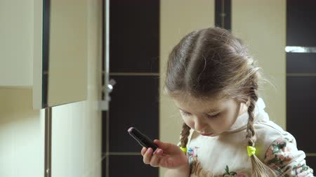 fonat : Little girl stands in front of mirror in the bathroom and doing makeup for herself. Adorable kid becomes like her adult mother. The girl is painting her lips with lipstick. Stock mozgókép