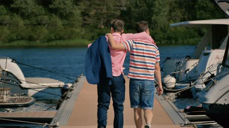 traje de passeio : Two young men walk at the pier. Two friends come to the yacht club to float on the yacht.