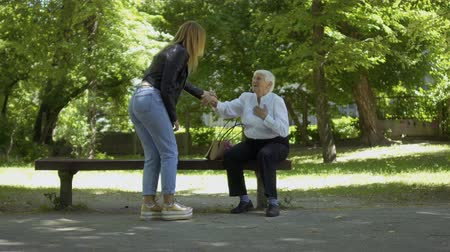 ambulância : Old woman with heart attack sit on the bench in park and asks help in passersby. Young girl not indifferent come to senior woman and help her to call in ambulance. Stock Footage