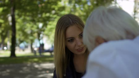 ambulância : Old woman with heart attack sit on the bench in park and asks help in passersby. Young girl not indifferent come to senior woman and help her to call in ambulance. Elderly woman take a pill from heart attack.