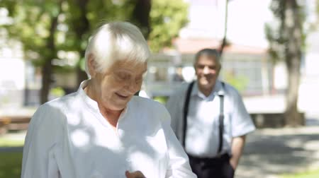 atender : Senior woman sprinkles parfume before the date with her man. Lovely old caouple have a meet in a summer park. Smiling man greeting his woman and people kisses. Stock Footage