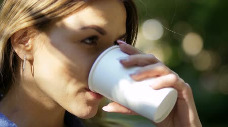 навынос : Young woman drinking coffee from disposable cup. Pretty blonde enjoy of drinking delicious beverage. Close-up. Slow motion.