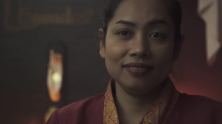 iyi giyimli : Charming Thai masseuse in a beautiful red dressing gown in a Thai massage salon. Close-up. Stok Video