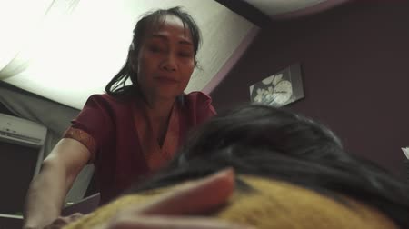 massagista : Charming Thai masseuse does hand massage to a young girl. Beautiful girl lies on a massage bed and enjoys a Thai massage in a Thai massage parlor. Close-up.