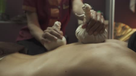 masaj : Thai massage with herbal pouches is a relaxing procedure. Thai with the use of herbal pouches. Close-up. Stok Video