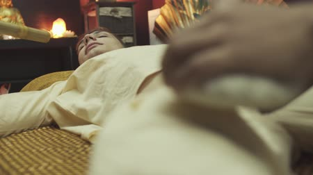 geri yaktı : Guy lies on the massage bed. Handsome boy getting foot massage with herbal pouches. Close-up. Stok Video