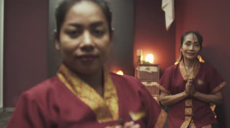 iyi giyimli : Two beautiful Thai masseuses in red dressing gowns in a massage salon. Candle burns in the background on a table. Close up.