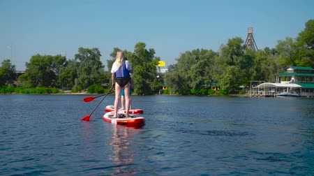 гребля : Brother and sister are kayaking on the river along the river. In front is the city beach. Стоковые видеозаписи