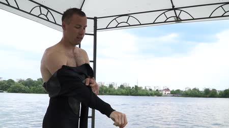 coletando : Handsome young man dressing in a wetsuit. Guy is preparing to ride on the water. Dark wetsuit on a beautiful guy. Vídeos