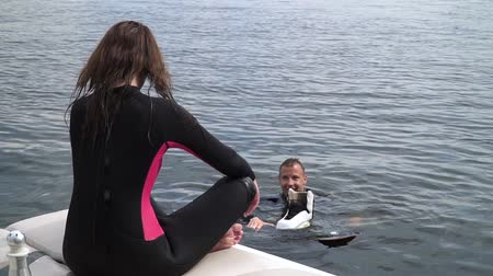 coletando : Beautiful girl and a handsome guy in wetsuits are actively resting on the river. Nice girl is sitting on the pier and the guy is swimming with wakeboard near. Stock Footage