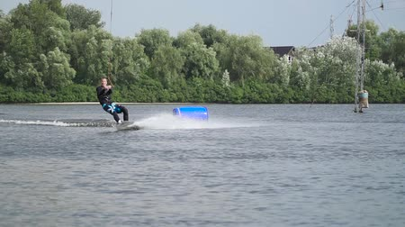 šňůra : Handsome guy in a wetsuit is riding a wakeboard on the river. Young man is actively resting.