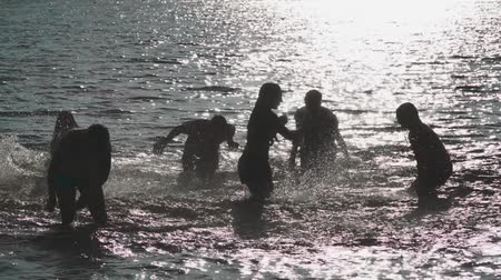 adolescência : Nice guys and girls having fun in the water. Young people have fun and are splashing water. Water splashes fly in all directions.