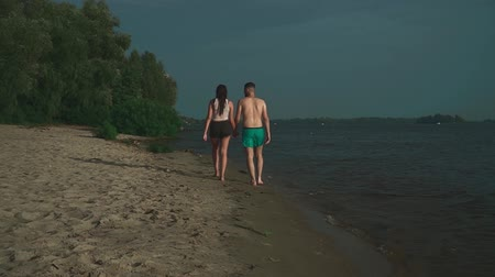 подростковый возраст : Young guy in swimming trunks and a beautiful brunette are walking along the river bank. Guy and a girl holding hands and walking. The pair moves away from the camera.