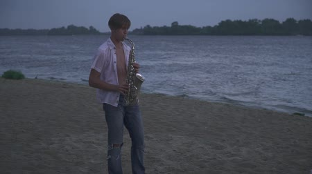saxofon : Handsome young guy is playing the saxophone on the river bank. Guy with an open white shirt on the beach. Dostupné videozáznamy