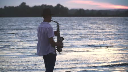 saxofon : Handsome young guy is playing the saxophone on the river bank. Guy with an open white shirt and in the hat on the beach. Beautiful river in the background. Dostupné videozáznamy