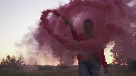 barevný : Blond young lady is circling in pillar of violet smoke. Woman is spraying colored smoke bomb in circular motions on open air. Using special decoration for video and photosessions. Spending time outdoors Dostupné videozáznamy