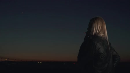 from behind : Blond lady in leather jacket is smoking in the background of night airport. At the sky light of airplane is blinking. Spending of time in late evening Stock Footage