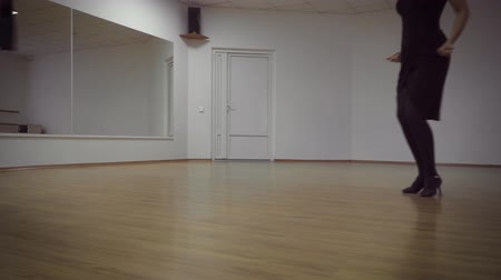 petite : Man and a woman are dancing in the studio. Handsome man and a charming girl dance beautifully. Choreographer and student. Spacious hall, wooden parquet and a mirror on the whole wall. Studio of dances. School of dance.