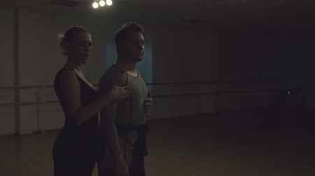 skarpetki : Man and a woman are dancing in the studio. Handsome man and a charming girl dance beautifully. Choreographer and student. Spacious hall, wooden parquet and a mirror on the whole wall. Couple dancing in the studio with muted light. School of dance. Wideo