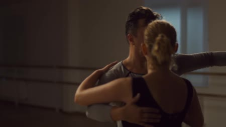 jimnastik : Man and a woman are dancing in the studio. Handsome man and a charming girl dance beautifully. Choreographer and student. Spacious hall, wooden parquet and a mirror on the whole wall. Couple dancing in the studio with muted light. School of dance. Stok Video