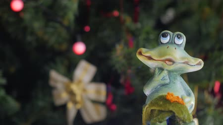 tree frog : Figure of a toy frog is spinning in front of the camera. Christmas tree with Christmas balls on the background. Close-up.