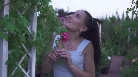 smelling : Adult beautiful brunette lady in white dress smells flower in the garden. Woman looks at the sky. Time pending outdoor at green garden. Female is smiling and happy Stock Footage