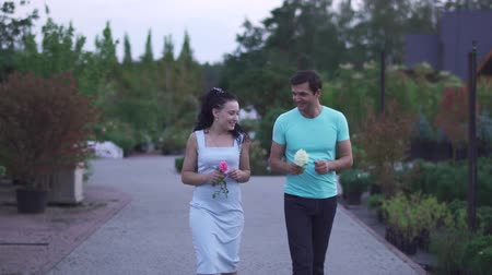 semana : Adult couple walks in the garden and smells flowers. Lovers spend time together outdoor. Pleasant walk near blossom bushes. People are happy together, both are smiling Vídeos