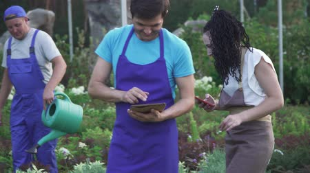 flowerpots : Workers of the garden center in work. Two guys and a girl are working in the garden center. A guy watering flowers using a watering can. The guy and the girl are recording information on the tablet and phone.
