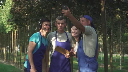 dinlenmek : Gardeners make selfie in the garden. Three men and woman have fun at work. People do their work carefully Stok Video