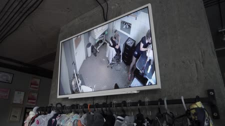 trimmelés : Video surveillance in grooming salon. Pet shop with grooming salon. Screen with groomers working. CCTV. Camera moves from left to right.