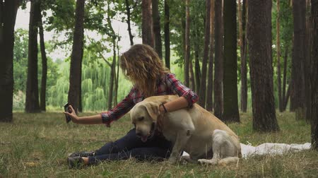 gadjet : Young lady is making selfie with her dog. Labrador is naughty and trying to lick human. Woman is spending time with the dog in forest. Rest with favourite pet outdoor.