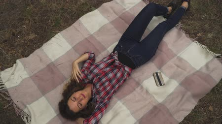 erişilebilirlik : Young woman with red hair is making selfie laying on blanket in the forest. Lady is posing in different ways. Spending time outdoor