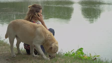 retriever : Curly woman and labrador is resting near the river. Lady is talking by mobile phone and her labrador is exploring ground. Rest with favourite pet outdoor.