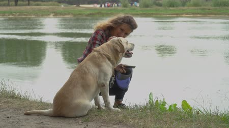 obediente : Curly woman and labrador is resting near the water. Girl gets up and makes dog sit at the ground. Rest with favourite pet outdoor. Stock Footage