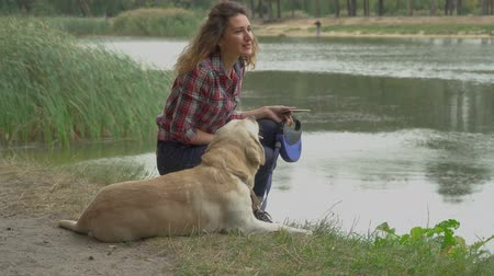 make friends : Curly woman and labrador is resting near the water. Girl gets up and makes dog sit at the ground. Rest with favourite pet outdoor. Stock Footage