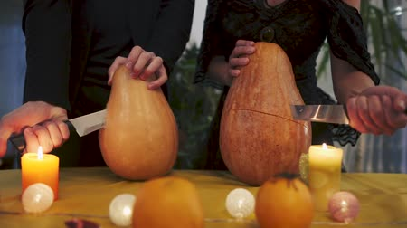 hallows : A woman and a man without a face in the frame thrust knives into the festive pumpkins. Mystical and terrible ritual of two unknowns on the night of Halloween. Halloween holiday. Stock Footage