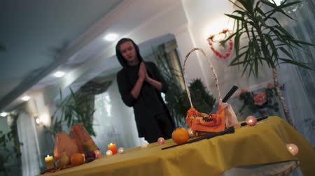rito : Halloween. Magician in the black hood casts a spell over the table. Young guy rubs his hands in front of the magic table. Halloween holiday.
