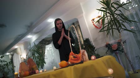 обряд : Halloween. Magician in the black hood casts a spell over the table. Young guy rubs his hands in front of the magic table. Halloween holiday.