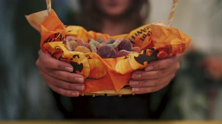 rito : Close-up of sweets basket. Girl takes the basket from the camera. Halloween holiday.