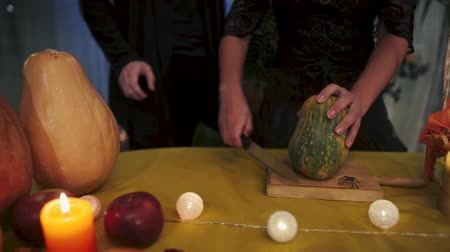 büyücü : Halloween. Mystical Halloween ritual. Girl in a black dress thrusts a knife into a pumpkin. Guy in black clothes grabs the hand of a witch with a knife. Halloween holiday.