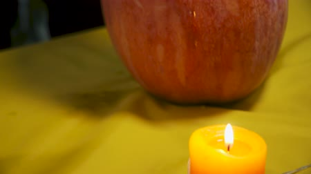 rito : Halloween. Burning candles, pumpkins and fruits on the table. Male hands put knife into pumpkin. Halloween holiday.