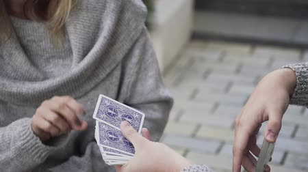 cheers : The guy shuffles the cards and the girl picks a card. Magician shuffles the cards Stock Footage