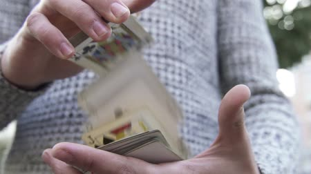 imbibe : Male hands show trick with a deck of cards. Man shuffle a pack of the cards. Illusionist shows focus. Focus with cards. Stock Footage