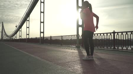 şeftali : Young athletic girl prepares for morning run on the bridge. The girl is running on the bridge in the morning. The lady spends time outdoor alone. The woman leads a healthy lifestyle. Female moves in slow motion. Stok Video