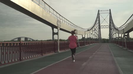 driveway : The girl is running on the bridge in the morning. The lady spends time outdoor alone. The woman leads a healthy lifestyle. Female moves in slow motion. Stock Footage