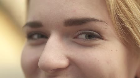 looking down : The girl looks in camera closeup. Woman with pretty face looks forward. Smiling eyes of a young girl close up Stock Footage